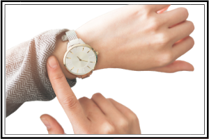 finger pointing to a watch on a wrist, wanting to be on time