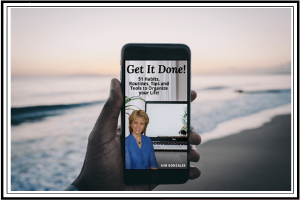 8 Ways To Be Productive Using Your iPhone! hand holding cellphone with book on screen display